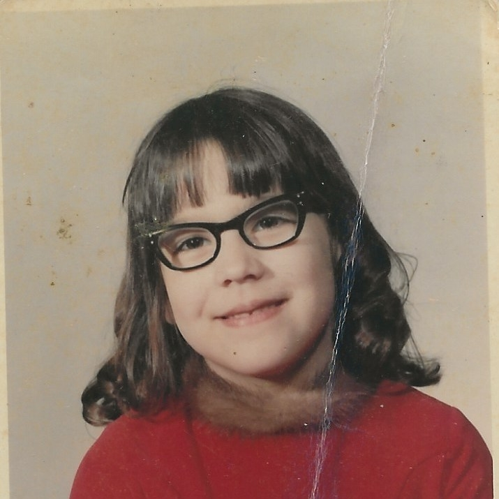 First grade school picture of little girl with brown bangs and glasses