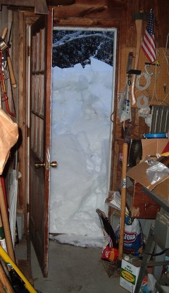 Snow is piled up in front of our back door in Maine.